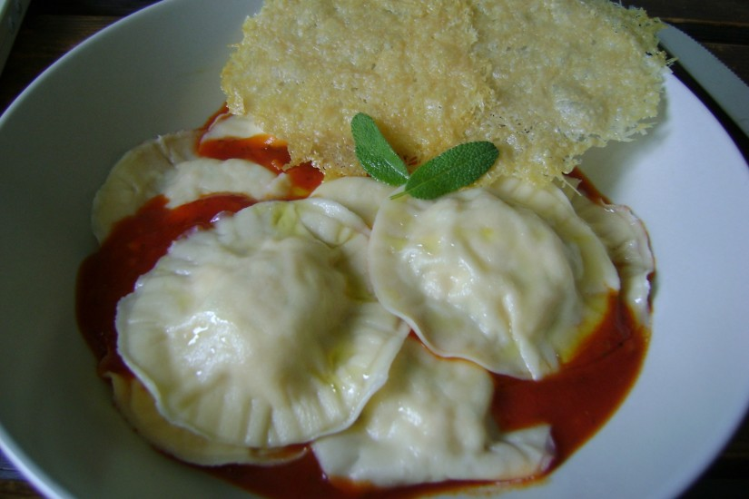 Zalm ravioli met tomatensaus en een parmezaankoekje